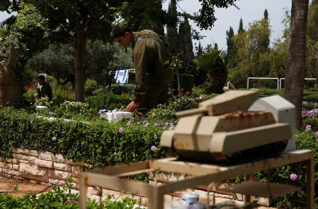 An Israeli soldier places a flag on the graves of fallen soldiers during a ceremony ahead of Memorial Day, commemorating those who died during conflicts, at the Kiryat Shaul military cemetery in Tel Aviv, Israel May 10, 2016. (Photo by Baz Ratner/Reuters)