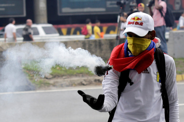An opposition supporter catches a tear gas bomb during clashes with riot policemen in a rally to demand a referendum to remove President Nicolas Maduro in Caracas, Venezuela, May 11, 2016. (Photo by Marco Bello/Reuters)