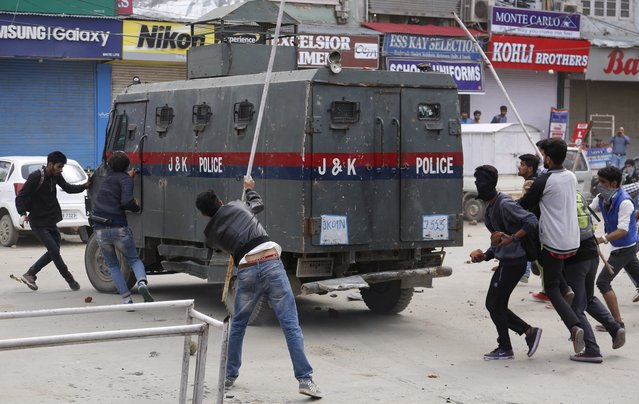 Kashmiri students and other protesters attack an Indian police vehicle as they clash in Srinagar, Indian controlled Kashmir, Monday, April 24, 2017. Tensions between Kashmiri students and Indian law enforcement have escalated since April 15, when government forces raided a college in Pulwama, about 30 kilometers (19 miles) south of Srinagar, to scare anti-India activists. (Photo by Mukhtar Khan/AP Photo)