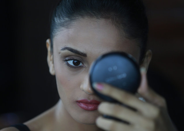 A model does her makeup as she waits for the audition of the upcoming Lakme Fashion Week in Mumbai, India, Wednesday, July 15, 2015. (Photo by Rafiq Maqbool/AP Photo)
