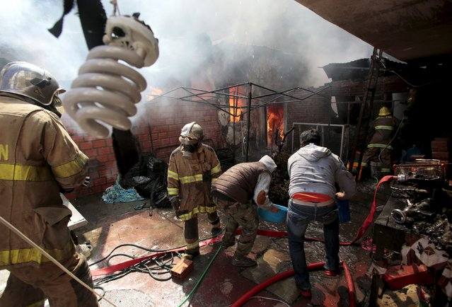Fire fighters and locals try to control a fire in a popular district of La Paz, Bolivia July 17, 2015. No injuries were reported according to local media. (Photo by David Mercado/Reuters)