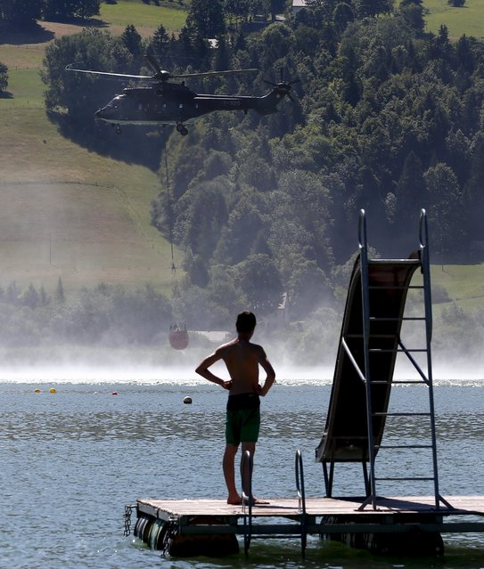 A Swiss Air Force Super Puma helicopter collects water from the Lac de Joux in Le Brassus, Switzerland, July 21, 2015. Due to the drought in Vaud County, authorities have requested the help of the Swiss military to deliver water to cattle farmers for 16 days. (Photo by Denis Balibouse/Reuters)