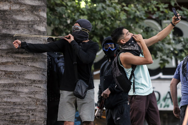 "A demonstrator makes a selfie as another one uses a sling against riot police during a protest against the government's economic policies in Santiago on November 6, 2019. Chile's president said Wednesday his government had ""nothing to hide"" concerning allegations that police killed, tortured and sexually assaulted civilians during deadly protests against him as protesters called on demonstrators to expand their rallies to rich districts so far untouched by the wave of demonstrations, centering on a major shopping center. (Photo by Javier Torres/AFP Photo)"