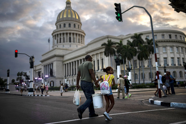 In this November 8, 2019 photo, people walk next to the Capital building, with its dome recently restored by Russian specialists in Havana, Cuba. (Photo by Ramon Espinosa/AP Photo)