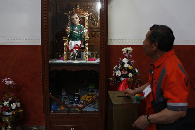 A man donates money near a baby Jesus statue dressed in a version of the national soccer team jersey at a church in Mexico City June 12, 2014. Catholic soccer fans pray before the statue, which believers say has granted miracles in the past, demanding him a good 2014 World Cup football match against Cameroon on June 13. (Photo by Tomas Bravo/Reuters)