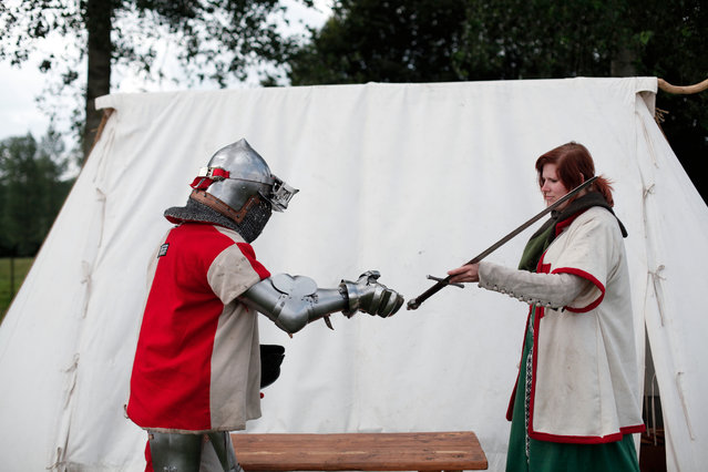 A woman gives a sword to a man dressed as a knight during a reenactment of the Battle of Agincourt, in Agincourt, northern France, Saturday, July 25, 2015. (Photo by Thibault Camus/AP Photo)