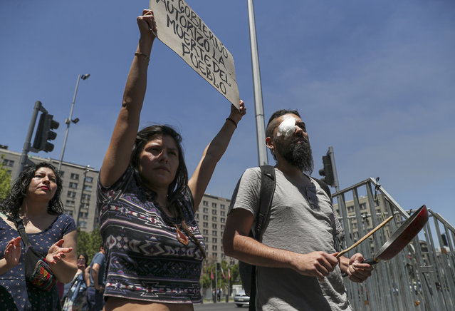 """Marcelo Herrera, his eye bandaged from an injury he received during recent protests, bangs on a pan as a woman holds a sign with a message that reads in Spanish: """"The government authorizes the murder of the People"""", during a demonstration in support of protesters who have been injured in the eye by Chilean police, in Santiago, Chile, Thursday, November 28, 2019. More than 230 anti-government protesters have suffered an eye injury since the social unrest began on Oct. 18. (Photo by Esteban Felix/AP Photo)"""