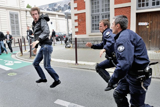 "Policemen chase away a protester during a demonstration of artists and entertainment workers, known as ""intermittents du spectacle"", near the Regional Directorate of Cultural Affairs (DRAC) on June 20, 2014 in Lille, northern France, to protest against the government's plans to reform their status. (Photo by Philippe Huguen/AFP Photo)"