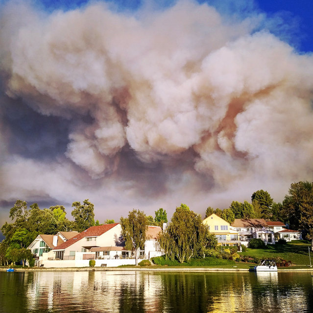 This photo provided by Matthew Dangerfield shows billowing smoke  from the Calabasas, Calif., fire as the clouds passed over the homes of Park Calabasas, Saturday, June 4, 2016. Los Angeles County fire officials now say a brushfire in the Calabasas neighborhood is threatening about 3,000 homes. Capt. Keith Mora tells KCAL-TV that's how many are near the 200-acre blaze that erupted Saturday afternoon northwest of downtown Los Angeles. He says about 200 homes and some 500 people are under mandatory evacuation but the others are strongly urged to leave the area, where flames up to 50 feet high rolled along ridgetops and torched trees right next to million-dollar homes. (Photo by Matthew Dangerfield via AP Photo)