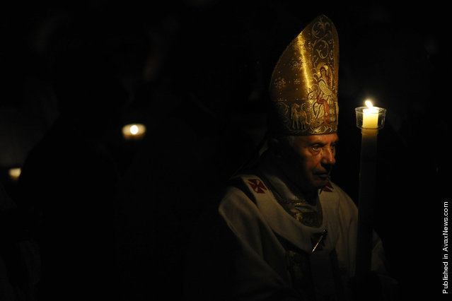 Pope Benedict XVI holds a candle during the Easter Vigil Papal mass on Holy Saturday on April 23, 2011, at St Peter's Basilica at The Vatican