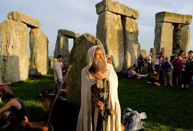 A druid waits for the sun to set during the summer solstice festival at Stonehenge, Salisbury, Britain, 20 June 2017. (Photo by Kim Ludbrook/EPA)
