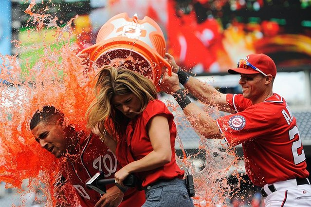 Ian Desmond, left, of the Washington Nationals is doused with Gatorade by his teammates as he is interviewed by MASN's Kristina Akra after hitting the game-winning sacrifice fly in the bottom of the 10th inning against the Miami Marlins at Nationals Park on April 21, Washington, D.C