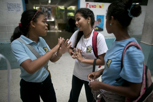 "In this May 31, 2016 photo, Maria Arias, center, shares a moment with classmates as they wait for their teacher to arrive for class at their public high school in Caracas, Venezuela. Arias lives in a violent neighborhood and has grown accustomed to her teachers not showing up for class. ""It's a trap,"" the 14 year-old complained. ""You risk your life to be here and end up waiting around for hours doing nothing. But you have to keep coming because it's the only way out"". (Photo by Ariana Cubillos/AP Photo)"