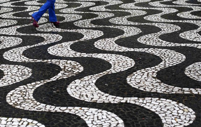 """A woman walks over patterned paving in central Porto Alegre during the 2014 World Cup in Brazil, June 26, 2014. In a project called """"On The Sidelines"""" Reuters photographers share pictures showing their own quirky and creative view of the 2014 World Cup in Brazil. (Photo by Darren Staples/Reuters)"""