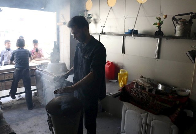 Abu Khaled, makes bread on a makeshift grill made from remnants of a rocket inside his shop in the Douma neighborhood of Damascus April 28, 2015. (Photo by Amer Almohibany/Reuters)