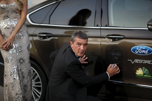 Spanish actor and director Antonio Banderas signs an autograph on a car next to his girlfriend Nicole Kimpel after their arrival at the Starlite Charity Gala in Marbella, near Malaga, southern Spain, August 9, 2015. (Photo by Jon Nazca/Reuters)