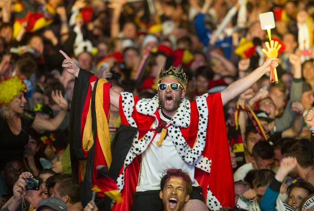 "German soccer fans react after the deciding goal for Germany in the final of the Brazil World Cup 2014 between Germany and Argentina played in Rio de Janeiro, Brazil, at a public viewing area called ""Fan Mile"" in Berlin, Sunday, July 13, 2014. (Photo by Steffi Loos/AP Photo)"