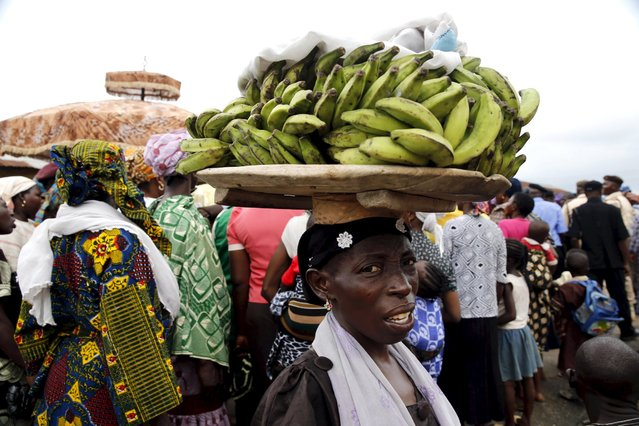 A woman carries bananas on a wooden tray on her head to sell during the traditional town cleansing procession at the start of the annual Osun festival in Osogbo in Nigeria's southwest, August 10, 2015. (Photo by Akintunde Akinleye/Reuters)
