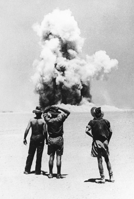 Australian soldiers watch a great cloud of smoke and sand rise in the western desert of Africa, June 1, 1941 marking the spot where they blew up a captured enemy ammunition dump. (Photo by AP Photo)