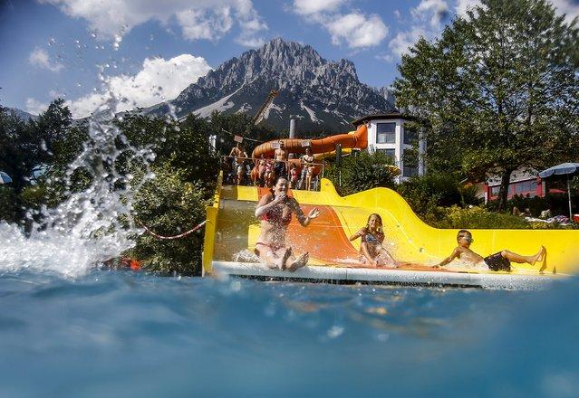 Children slide down a water slide on a hot summer day in the western Austrian village of Ellmau, August 12, 2015. (Photo by Dominic Ebenbichler/Reuters)
