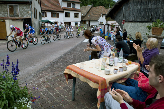 Cyclists ride as supporters cheer during the 170 km ninth stage of the 101st edition of the Tour de France cycling race on July 13, 2014 between Gerardmer and Mulhouse, eastern France. (Photo by Eric Feferberg/AFP Photo)