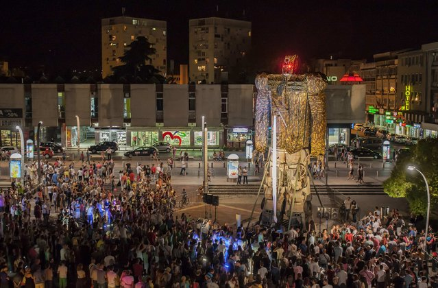 "Crowds gather to look at a 14 metre (46 feet) sculpture weighing 25 tons (22679 kg) ""Megatron"", a Transformer-inspired sculpture constructed from scrap metal, at main square in Podgorica, July 23, 2014. Danilo Baletic, 22, makes sculptures of his childhood cartoon heroes ""Transformers"" from scrap metal. In the last two years, he has made seven ""Transformers"" that are placed on the streets of Montenegro's capital Podgorica as part of an exhibition called ""Transformers defending Podgorica"". (Photo by Stevo Vasiljevic/Reuters)"