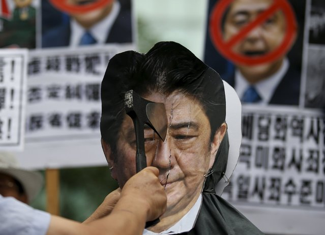 A protester chops an effigy of Japanese Prime Minister Shinzo Abe with an axe during an anti-Japan rally on the occasion of the 70th anniversary of liberation from Japan's 1910-45 colonial rule, on Liberation Day in Seoul, South Korea, August 15, 2015. (Photo by Kim Hong-Ji/Reuters)