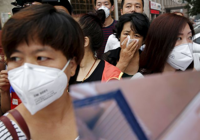 Residents evacuated from their homes after last week's explosions in Binhai new district wear face masks as they take part in a rally demanding government compensation outside the venue of the government officials' news conference in Tianjin, China, August 18, 2015. (Photo by Kim Kyung-Hoon/Reuters)