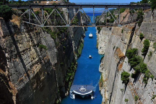 "The world's largest solar-powered boat, ""MS Turanor PlanetSolar"" sails through the Corinth Canal near the town of Corinth on July 28, 2014. The boat arrived to Greece as part of a joint archaeological project focused on underwater exploration off one of Europe's oldest human occupation sites, the Franchthi cave in the Argolid, southeast Peloponnese. (Photo by Valerie Gache/AFP Photo)"