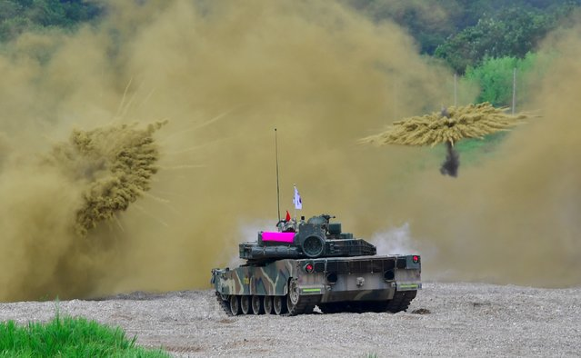 South Korea's K-1 tank fires smoke shells during a joint military drill between US and South Korean Marines at a fire training field in the southeastern port of Pohang on July 6, 2016. South Korea and the United States are conducting a joint marine infiltration and attack exercise, testing the interoperability of the two countries' forces for a potential operation against North Korea. (Photo by Jung Yeon-Je/AFP Photo)