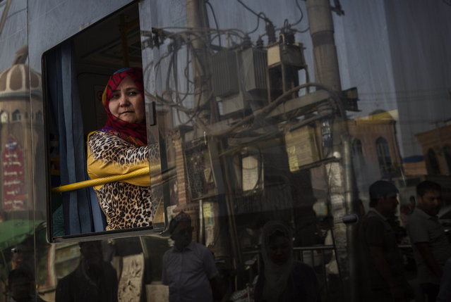 A Uyghur woman looks out the window as she rides in a new bus on August 1, 2014 in old Kashgar, Xinjiang Province, China. (Photo by Kevin Frayer/Getty Images)