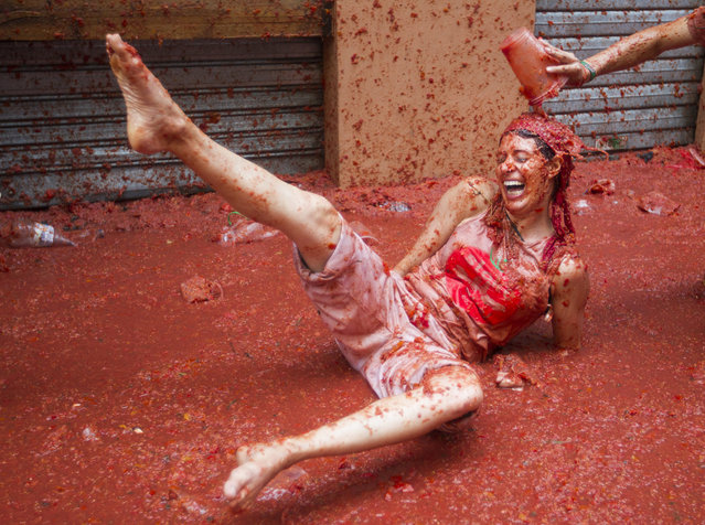 "A reveller covered in tomato pulp takes part in the annual ""Tomatina"" festival in the eastern town of Bunol, on August 30, 2017. The iconic fiesta – which celebrates its 72nd anniversary and is billed at ""the world's biggest food fight"" – has become a major draw for foreigners, in particular from Britain, Japan and the United States. (Photo by Jaime Reina/AFP Photo)"