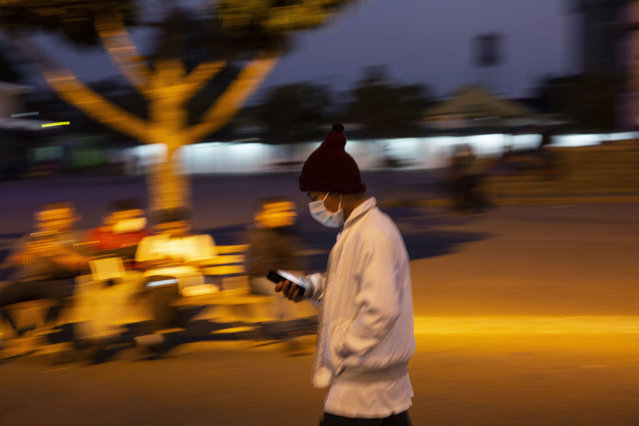 A man wearing a face mask as a precaution against the spread of the new coronavirus, walks near a bus station in Guatemala City, Thursday, March 19, 2020. As part of emergency measures due to the COVID-19 pandemic, the Guatemalan government has restricted public transportation. (Photo by Moises Castillo/AP Photo)