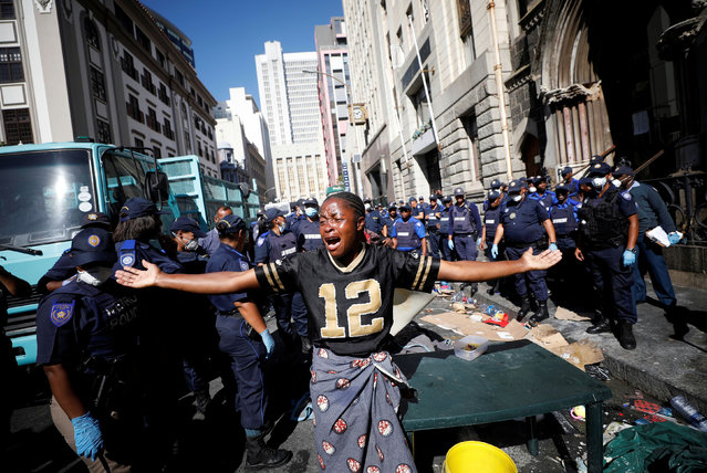 A woman wails as law enforcement officials move in to disperse a group of immigrants who had occupied a historic church and a square demanding to be moved to another country as they claimed to feel not safe because of xenophobic attacks, in central Cape Town South Africa, March 1, 2020. (Photo by Mike Hutchings/Reuters)