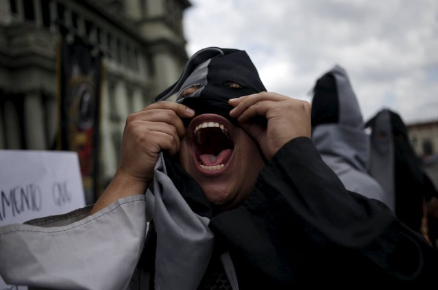 A hooded student of the San Carlos University of Guatemala shouts slogans during a demonstration against the government of the Guatemalan President Otto Perez Molina, in front of the Presidential Palace in Guatemala City, August 28, 2015. (Photo by Jorge Dan Lopez/Reuters)