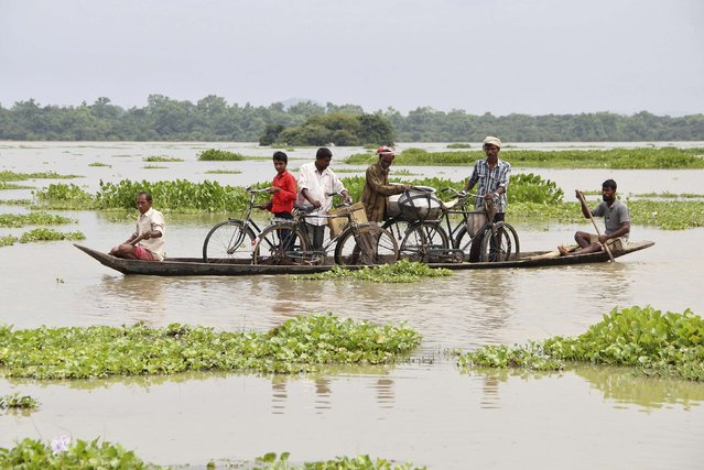 Villagers transport their bicycles on a boat through the flooded areas of Morigaon district in the northeastern Indian state of Assam August 18, 2014. The latest heavy rains have caused landslides and floods in many parts of India and Nepal, where at least 90 people have been killed since Thursday. (Photo by Reuters/Stringer)