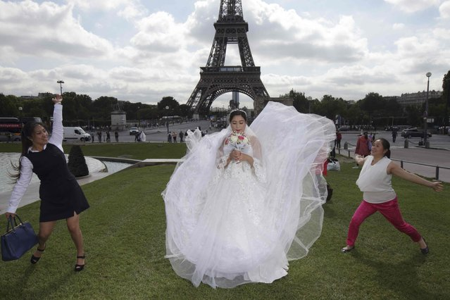 A Chinese future bride has her friends playing with her dress during a pre-wedding photoshoot in front of the Eiffel tower in Paris, France, August 28, 2015. (Photo by Philippe Wojazer/Reuters)