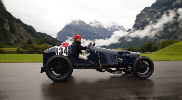 A participant arrives on his vintage Riley sports car during the British Car Meeting in the village of Mollis, east of Zurich, on August 24, 2014. Some 1,300 owners of vintage British cars took part in the annual meeting. (Photo by Arnd Wiegmann/Reuters)