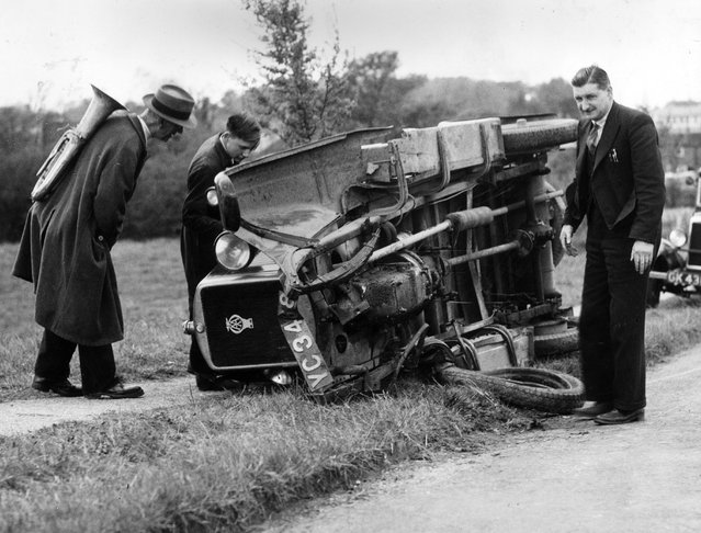 Passers by peer into an overturned car lying on the verge on the Fareham – Southampton road in Hampshire. No one was hurt in the accident. 19th May 1938. (Photo by E. Phillips/Fox Photos)