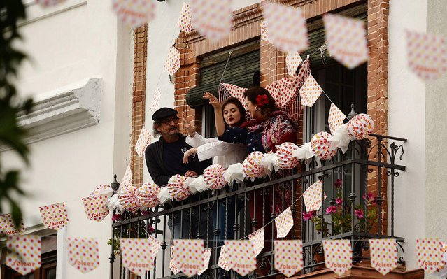 People mark traditional April Fair from their adorned balconies on April 24, 2020 due to a national lockdown to prevent the spread of the COVID-19 disease in Seville. Spain's daily virus toll rose slightly on April 25, 2020 with 378 people dying, the government said a day after the country registered its lowest number of fatalities in four weeks. The number was slightly higher than Friday's figure of 367, hiking the overall death toll in Spain to 22,902, the third-highest figure in the world after the United States and Italy. (Photo by Cristina Quicler/AFP Photo)