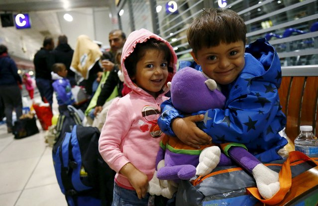 Two Syrian children laugh as they cuddle a stuffed toy given by wellwishers after they arrived with a train from Budapest's Keleti station at the railway station of the airport in Frankfurt, Germany, early morning September 6, 2015. (Photo by Kai Pfaffenbach/Reuters)