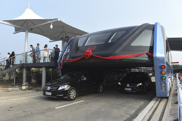 In this Tuesday, August 2, 2016 photo released by Xinhua News Agency, people stand on a platform as the Transit Elevated Bus TEB-1 conducting a test run after it unveiled in Qinhuangdao, north China's Hebei Province. The 72-feet long and 25-feet wide Transit Elevated Bus (TEB) powered by electricity can carry more than hundreds passengers, is designed to go over the normal traffic to help ease traffic congestion without having to dig new tunnels or build elevated rail tracks. (Photo by Luo Xiaoguang/Xinhua via AP Photo)