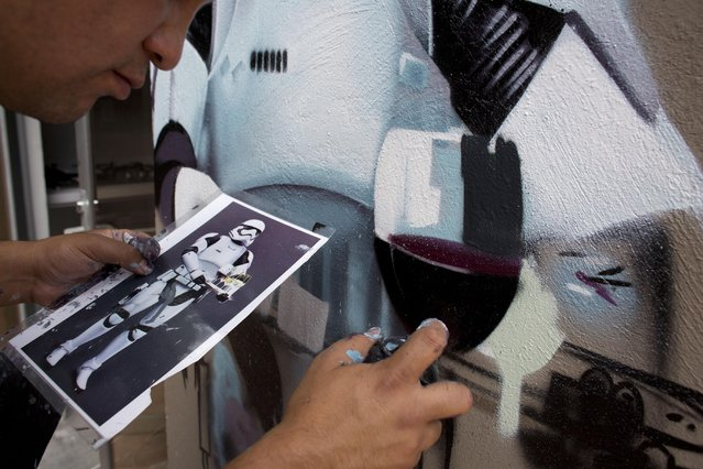 """In this September 1, 2015 photo, artist Andrik Figueroa Barreto, also known as Andrik Noble, paints a storm trooper holding a tray of wine glasses, on the roof terrace of an architect's office in the San Miguel Chapultepec neighborhood of Mexico City, as part of the Street Art Chilango cooperative's efforts to fill neighborhoods with street art. """"I don't have any studio. Everything is in the street"""", said Noble, whose hands, t-shirt, and shorts were covered in paint smudges of a dozen different colors. (Photo by Rebecca Blackwell/AP Photo)"""