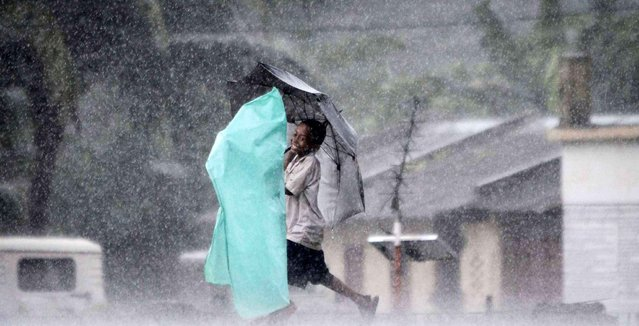 A village boy holds an umbrella and walks in the rain with another, wrapped in a plastic sheet, on the outskirts of Bhubaneswar, India, Wednesday, September 10, 2014. (Photo by Biswaranjan Rout/AP Photo)