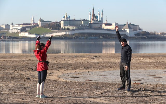 Warming up before a morning jog along the waterfront of the Kazanka River in Kazan, Russia on May 3, 2020. Starting from May 1, individual physical exercise once a day between 5 and 7am is available among the options covered by the digital pass system introduced by Tatarstan amid the ongoing COVID-19 pandemic. (Photo by Yegor Aleyev/TASS)