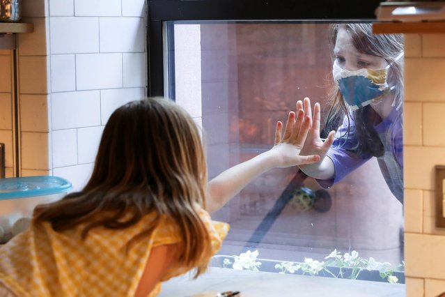 Lydia Hassebroek says hi to her friend Rose through her kitchen window during the outbreak of the coronavirus disease (COVID-19) in Brooklyn, New York, U.S., May 17, 2020. (Photo by Caitlin Ochs/Reuters)