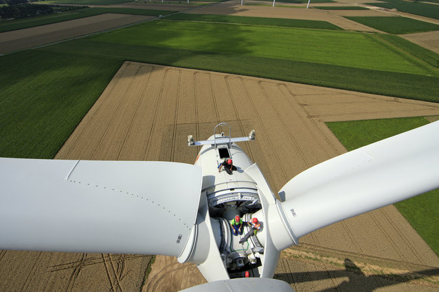 Employees work on the top of a turbine in Meneslies, France July 31, 2014. (Photo by Benoit Tessier/Reuters)