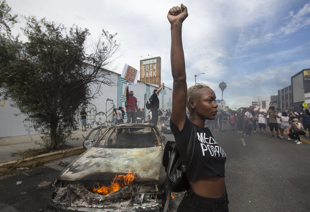 A protester poses for photos next to a burning police vehicle in Los Angeles, Saturday, May 30, 2020, during a demonstration over the death of George Floyd. a black man who was killed in police custody in Minneapolis on May 25. (Photo by Ringo H.W. Chiu/AP Photo)