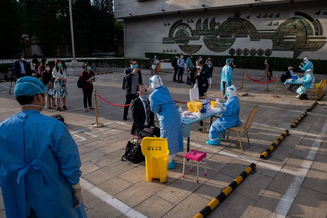 Medical workers wearing full protective gear prepare to take swab samples from journalists to test for the COVID-19 coronavirus, nine hours before the press conference of China's Foreign Minister Wang Yi during the National People's Congress (NPC) in Beijing on May 24, 2020. All journalists accredited to cover the CPPCC and National People's Congress events have to pass the COVID-19 test. (Photo by Nicolas Asfouri/AFP Photo)