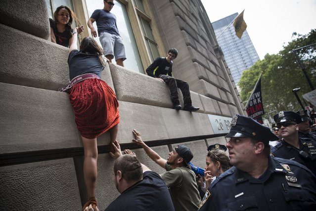 Protesters calling for massive economic and political changes to curb the effects of global warming climb down from a building's ledge after leading chants on Broadway around the Wall Street Bull statue on September 22, 2014 in New York City. Approximately 2,600 protesters participated; despite blocking traffic on numerous streets few arrests have taken place. (Photo by Andrew Burton/Getty Images)